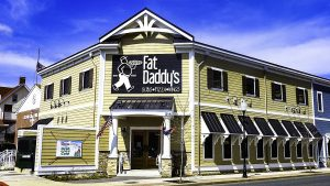 A yellow and black building for Fat Daddy's Restaurant
