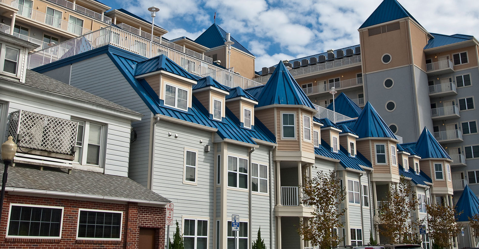 Smaller condominiums with roof access next to a much larger condominium building