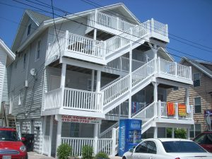 A repaired 8th street building with new white decking and stairs