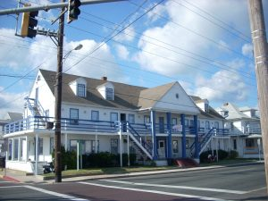 A rundown white and blue building with blue columns and stairs