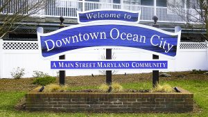 "A sign that says ""Welcome to Downtown Ocean City A Main Street Maryland Community"" in white lettering"