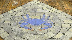 A brick paved blue crab in the boardwalk